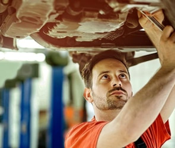 aaa mechanic works on a car in the body shop