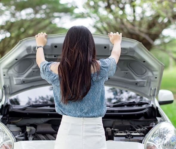 a AAA Member checks her car battery on the side of the road