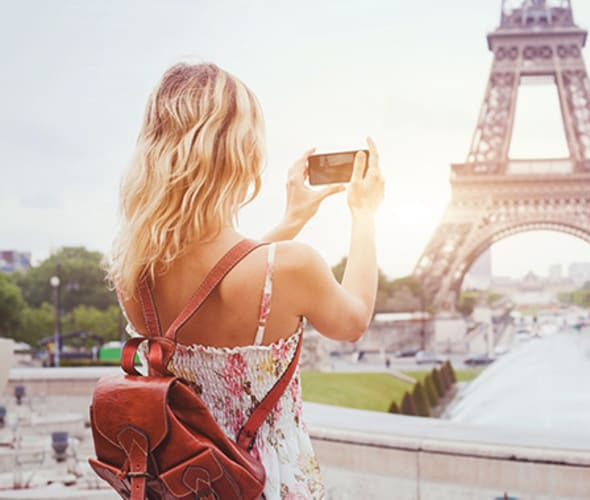 woman on vacation in paris takes picture of eiffel tower with her camera