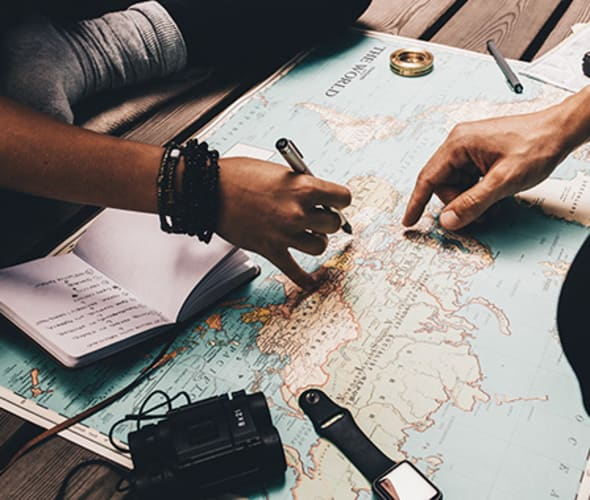 friends plan a trip with AAA travel resources and a map of the world