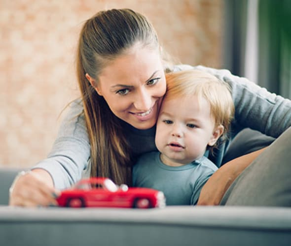 a mom with AAA life insurance plays on the couch with her toddler son