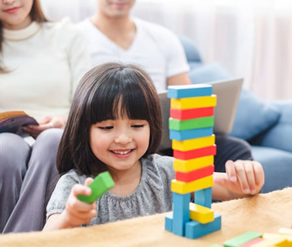 a girl plays with legos in her house insured with AAA