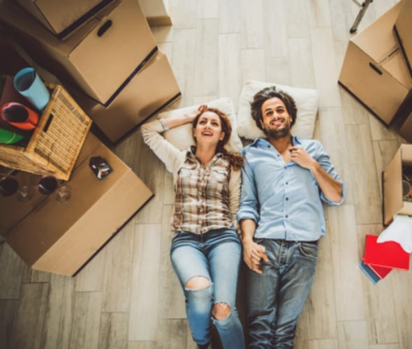 a couple with aaa membership rests on the floor of their new home after moving with aaa discounts