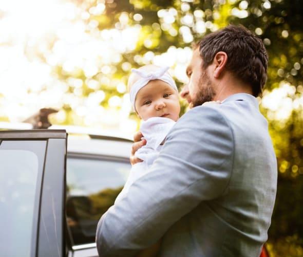 a caregiver walks a baby to a car