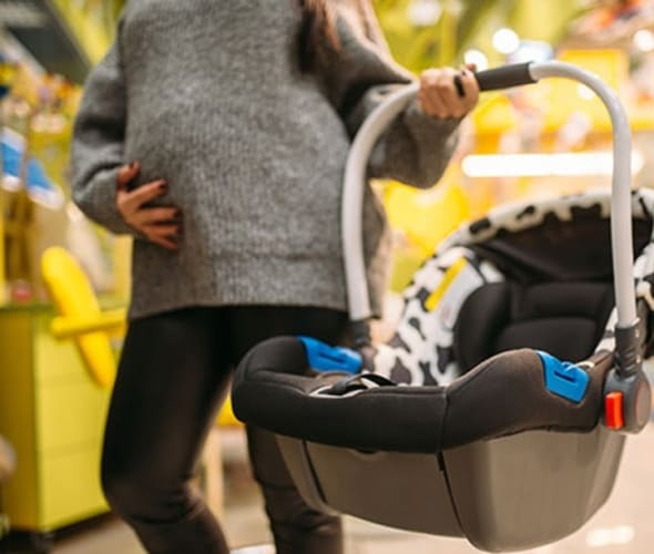 an expecting mother shops for a car seat