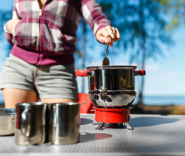 A woman cooks on her camping stove on a picnic table.