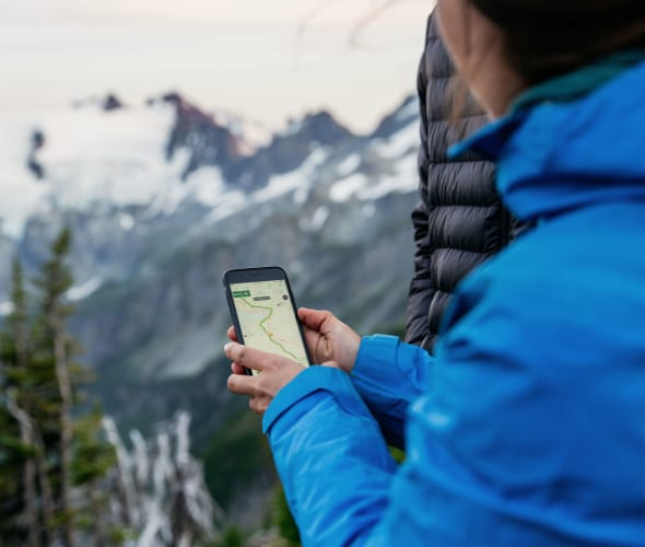 A woman uses Gaia GPS when hiking in the spring.