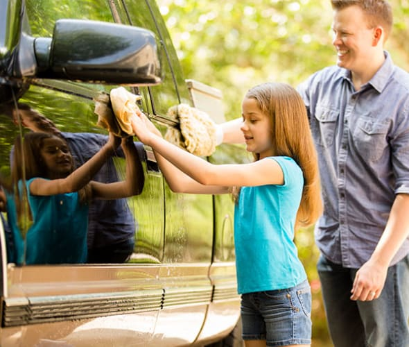 a father and daughter wash a pickup truck
