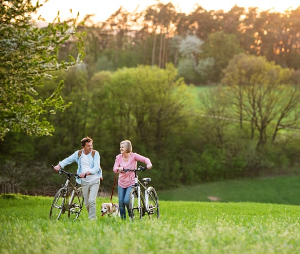 Couple with ExpressTerm life insurance through AAA walking bikes through a field