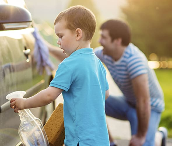a son and kneeling father wash a car together