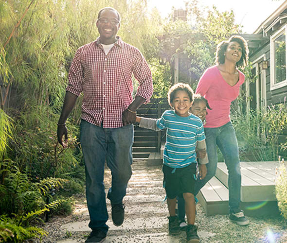 a smiling family while the son leads the parents the side yard