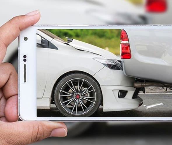 AAA member taking a picture on a cell phone of a car that rear-ended another vehicle
