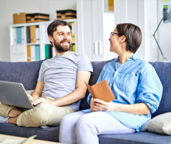 couple laughing while sitting on a blue sofa in their home covered by AAA homeowners insurance