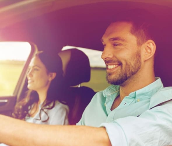 close up of a couple driving in a car covered by AAA auto insurance