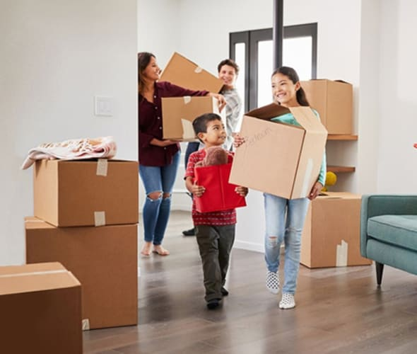 family of four carrying moving boxes into their new home covered by AAA homeowners insurance