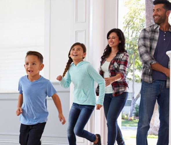 mother, father and two children walking through the front door of their home covered by aaa homeowners insurance