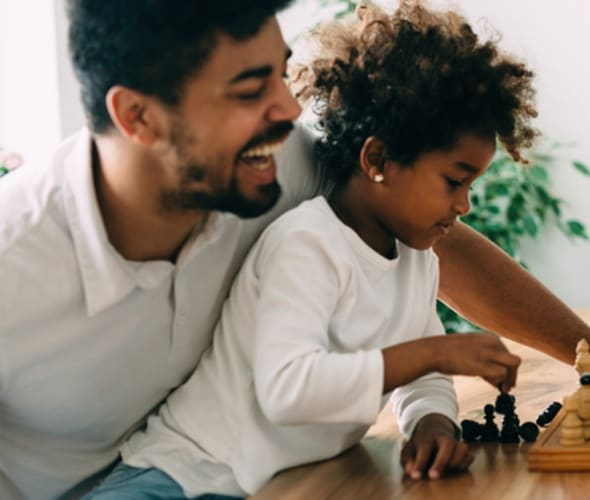 father laughing while teaching daughter to play chess in their home protected by AAA homeowners insurance
