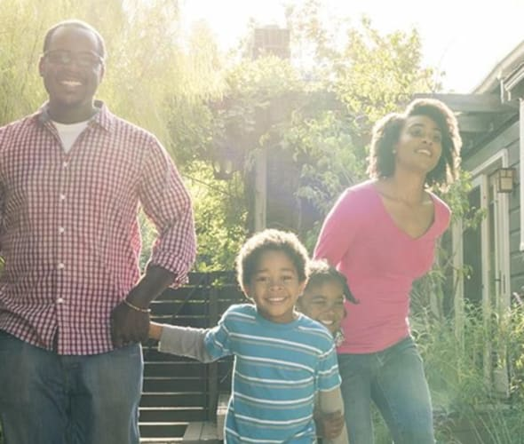 family holding hands outside of their home protected by AAA homeowners insurance