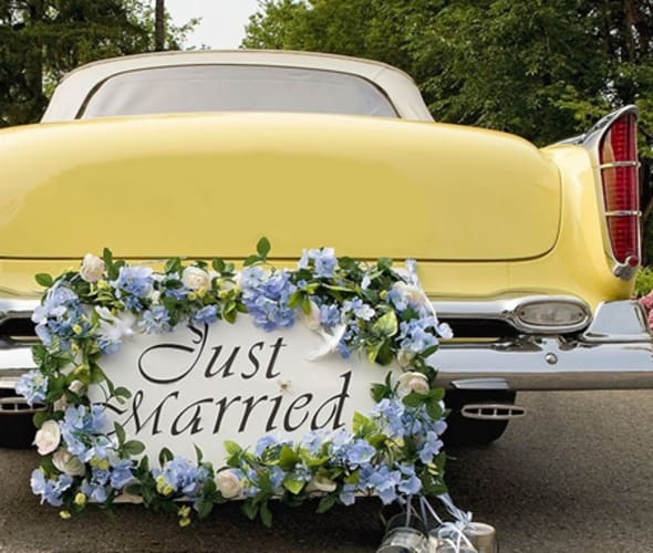 yellow antique car with a just married sign on the back bumper