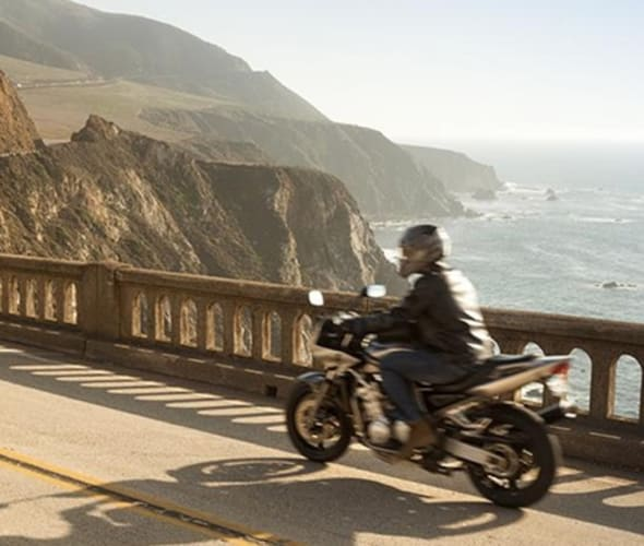 aaa member riding a motorcycle over a bridge with cliffs in the distance