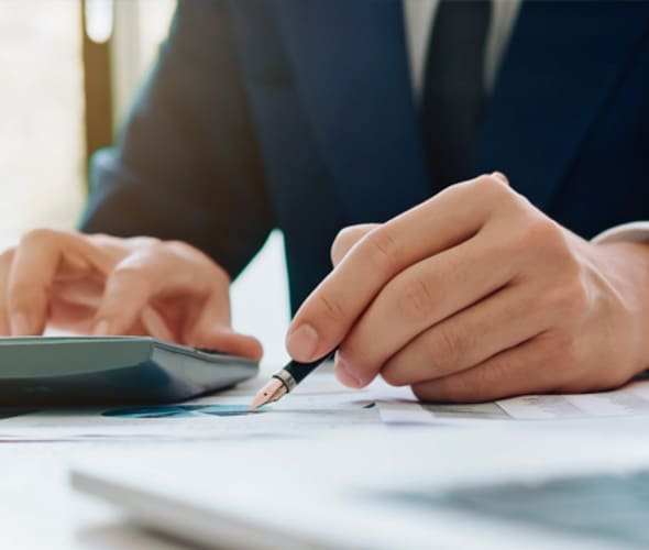 business person using a calculator to determine closing costs on a new home