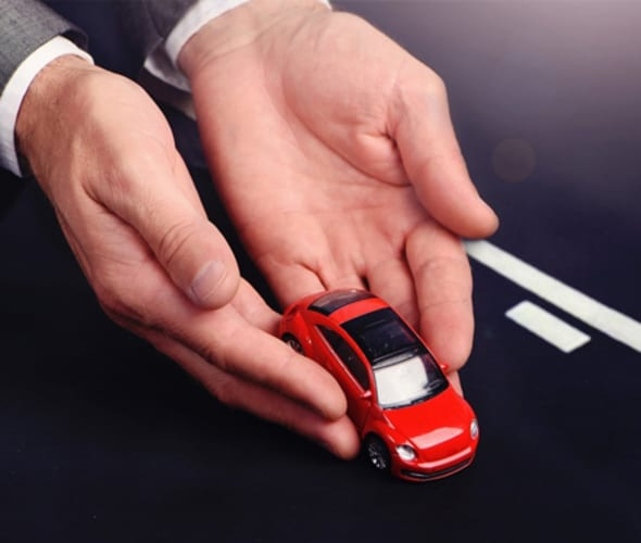 hands holding a red toy car over a toy roadway