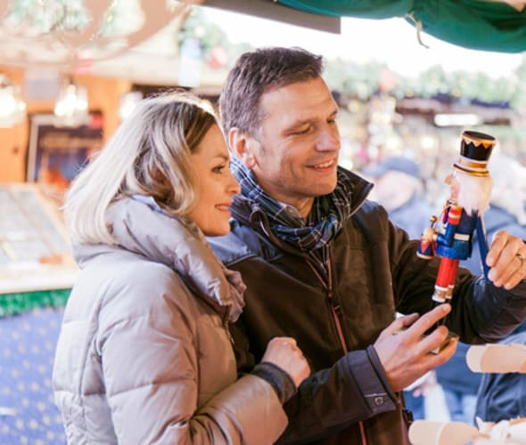 couple exploring a christmas market in europe on an amawaterways river cruise