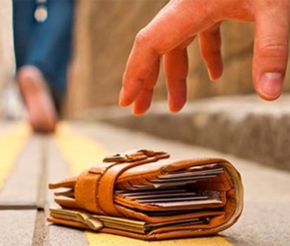 a person picks up a wallet from the ground
