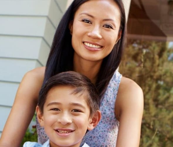 Mother and son sitting in front of house covered by AAA renters insurance