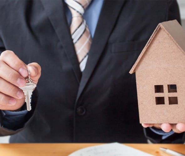 Man in a business suit holding out the keys to a new home