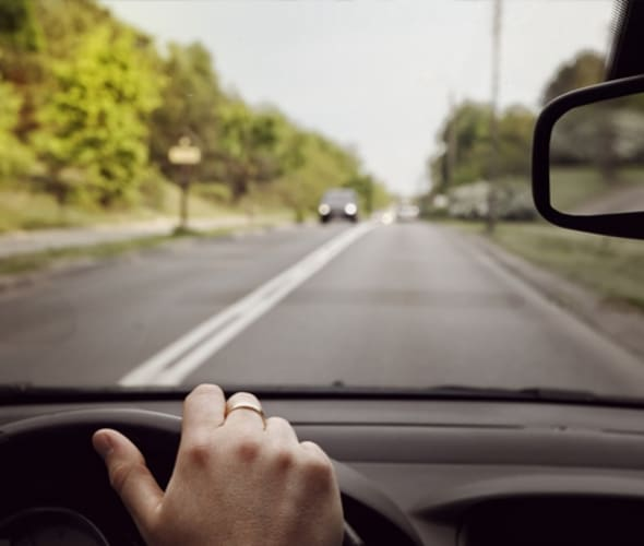 hands on the wheel looking out on green suburban street through windshield