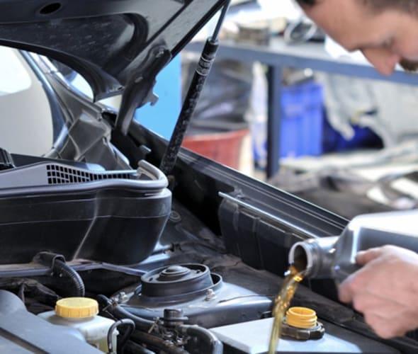 auto mechanic pours oil into a car engine