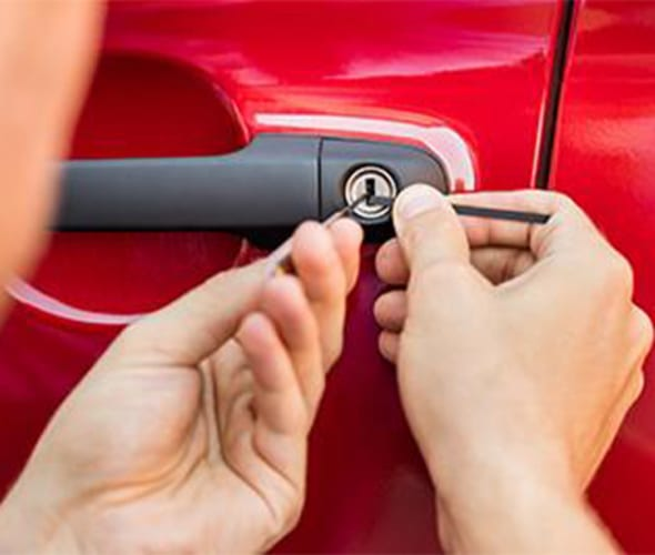 a man uses a lock pick to get into a red car door