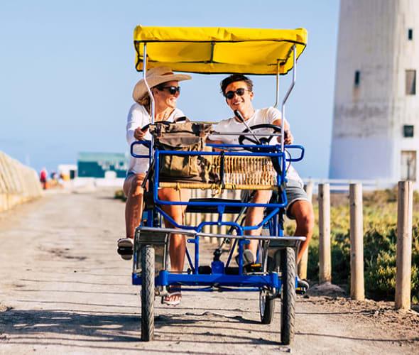 A AAA Universal Life Insurance customer and her son bike along a sunny beach