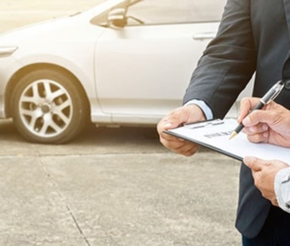 A driver with AAA insurance fills out a form after a car accident