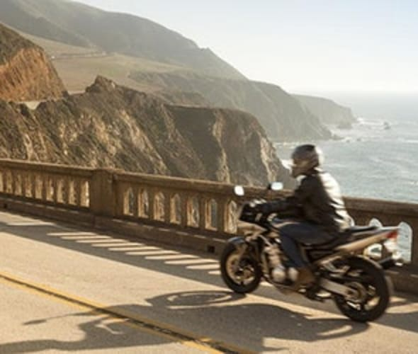 a motorcyclist with AAA specialty insurance drives down highway 1 in Big Sur on the California coast