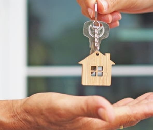 a landlord with AAA rental property insurance hands over keys to an apartment