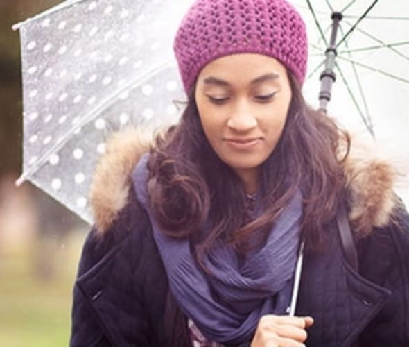 A woman with AAA personal umbrella protection insurance stands under an umbrella in the rain