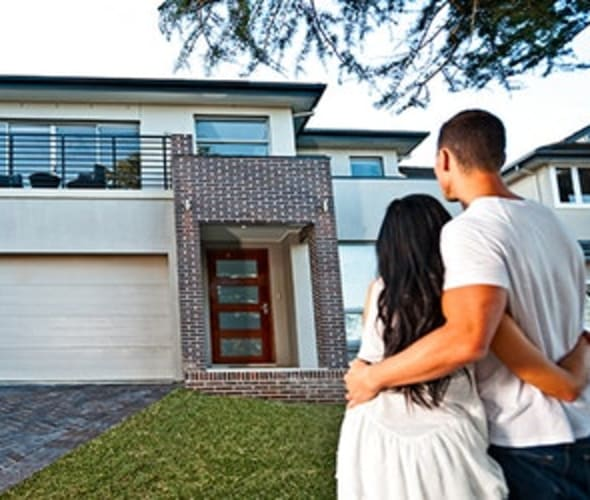a couple stands in front of their new home  with AAA homeowners and earthquake insurance