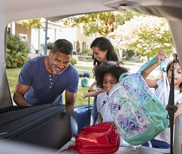 family placing luggage in dollar rental car