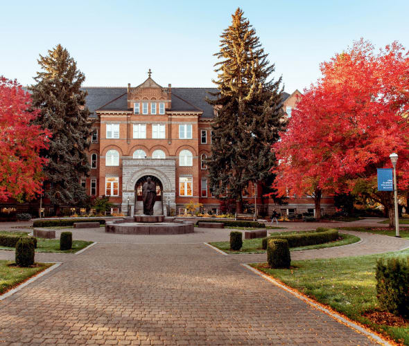 College Hall at Gonzaga University in Spokane, Washington surrounded by trees with red leaves.