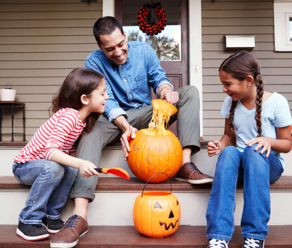 A dad carves a pumpkin with his daughters on their porch.