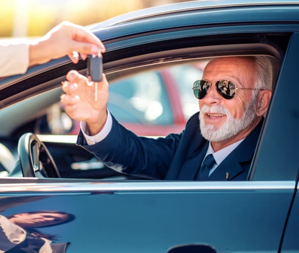 A senior man is handed the key to his new car.