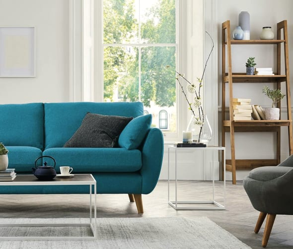 teal couch in a bright white living room with pale rug and gray chair.