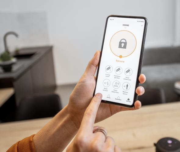 a hand holds a smartphone and uses a home security app.